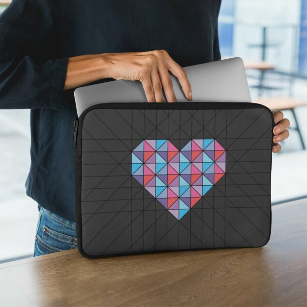 person holding a laptop sleeve with a geometric pink and blue heart design with a black background
