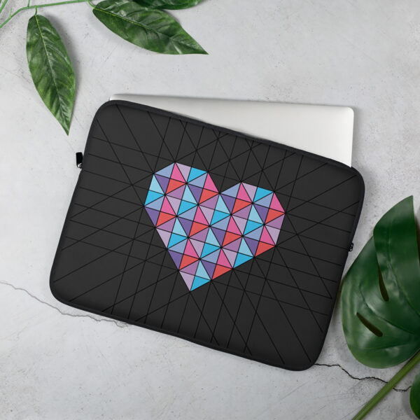 laptop sleeve with a geometric pink and blue heart design with a black background sitting on a table