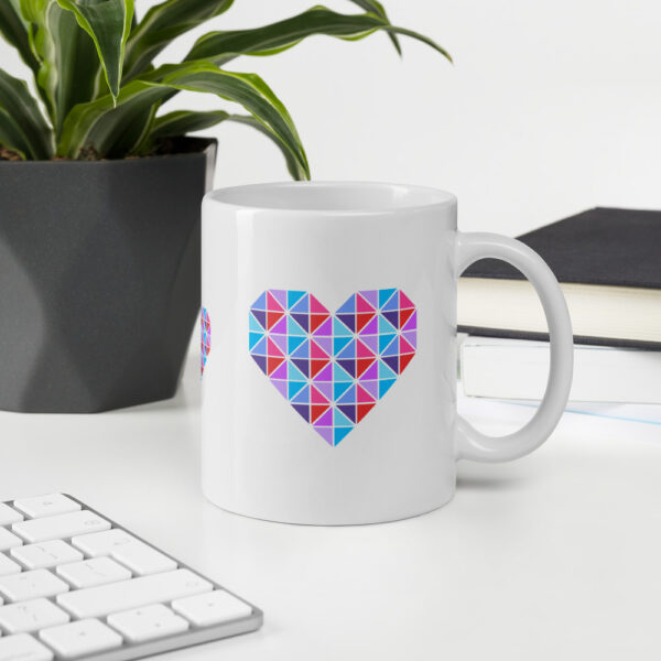 11 ounce white ceramic coffee mug with a geometric pink and blue heart design on the side sitting on a desk