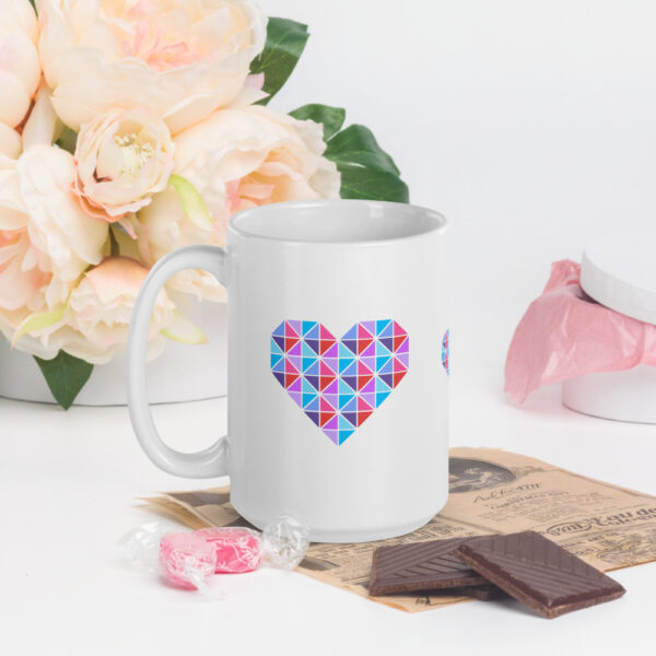 15 ounce white ceramic coffee mug with a geometric pink and blue heart design on the side sitting next to candy