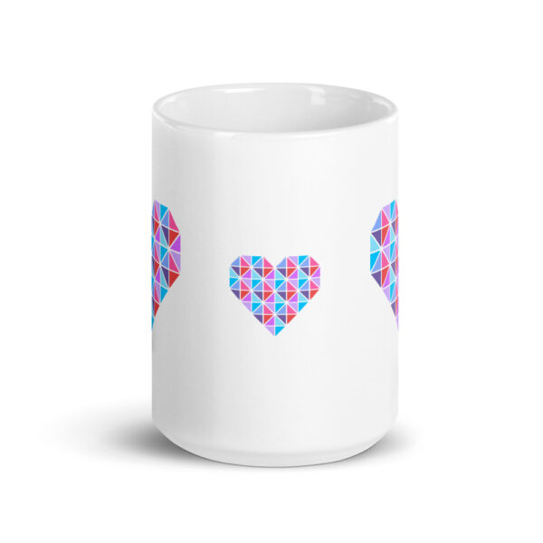 side view of a white ceramic coffee mug with three geometric pink and blue hearts design on the side