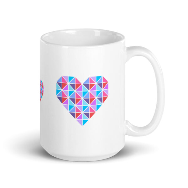 15 ounce white ceramic coffee mug with a geometric pink and blue heart design on the side