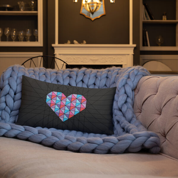 rectangle pillow with a pink and blue geometric heart design on a black background sitting on a sofa