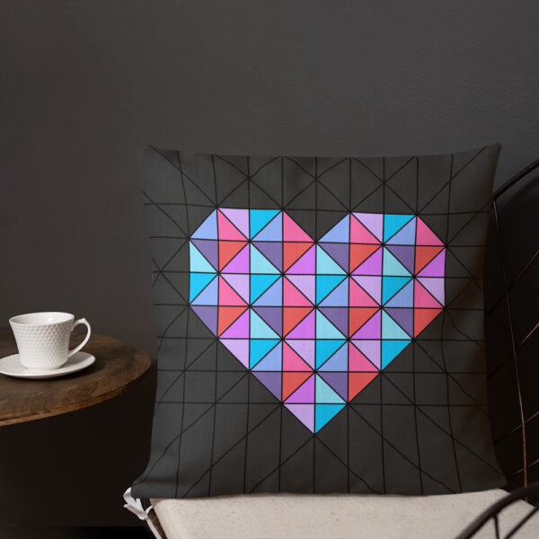square pillow with a pink and blue geometric heart design on a black background sitting on a chair next to a cup of coffee