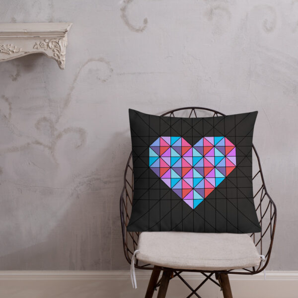 square pillow with a pink and blue geometric heart design on a black background sitting on a chair