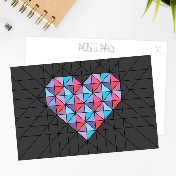 postcard with a pink and blue geometric heart design on a black background sitting on a desk