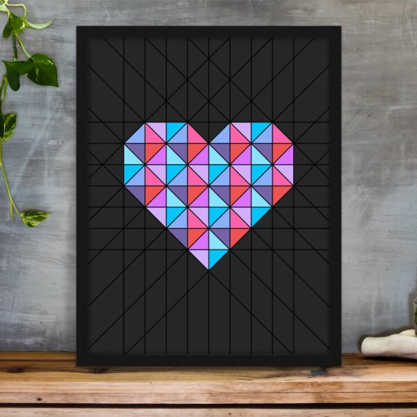 vertical fine art print of a pink and blue geometric heart design on a black background in a black frame on a table