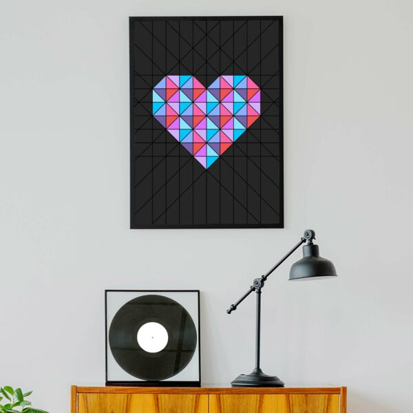 vertical fine art print of a pink and blue geometric heart design on a black background in a black frame hanging on a wall