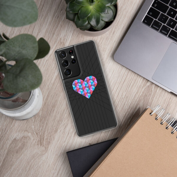 samsung phone case with a pink and blue geometric heard design on a black background sitting next to a laptop