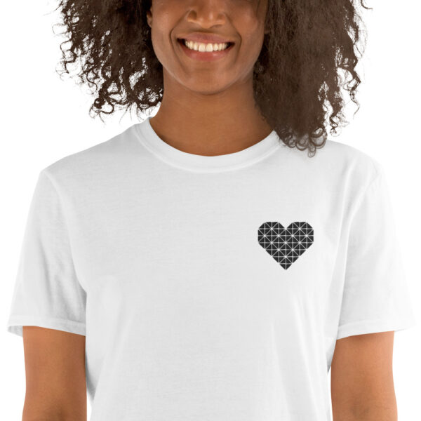 woman wearing a white t-shirt with a black geometric heart embroidered on the left chest