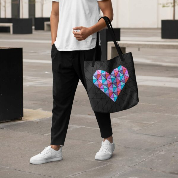 person holding a black tote bag with a geometric pink and blue heart design and black handles
