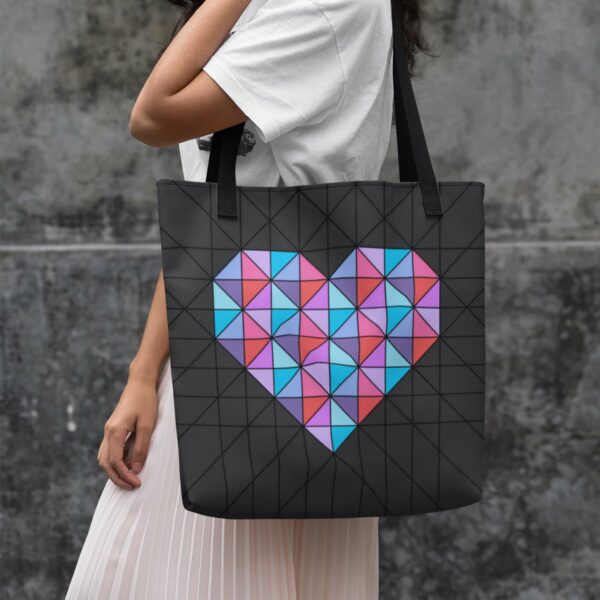 woman holding a black tote bag with a geometric pink and blue heart design and black handles
