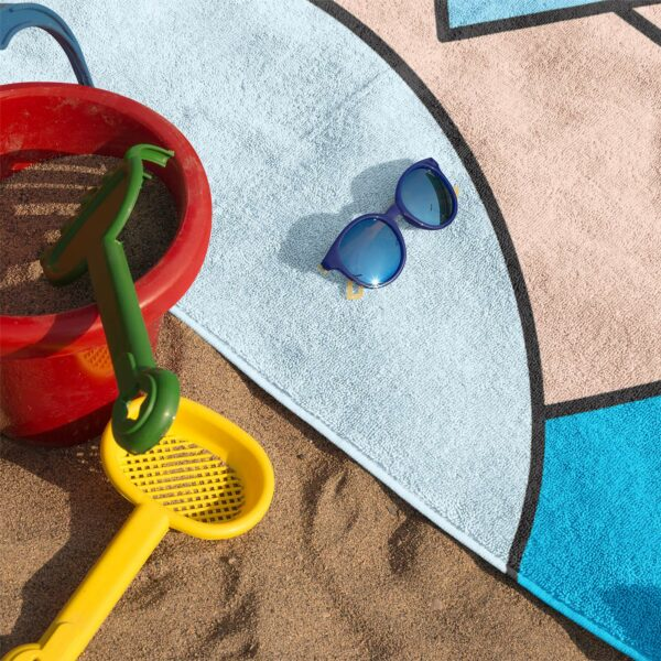 beach towel with an abstract design of blue and peach colored shapes on sand with sunglasses