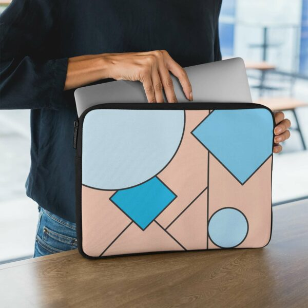 person holding a laptop sleeve with an abstract design of blue and pink shapes