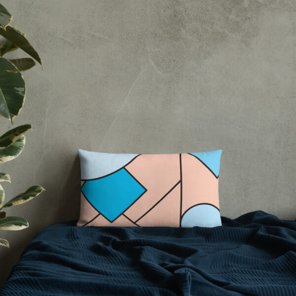 rectangle pillow with an abstract design of blue and pink shapes sitting on a bed