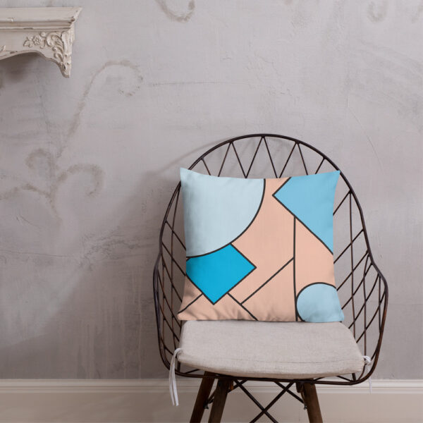 square pillow with an abstract design of blue and pink shapes sitting on a chair