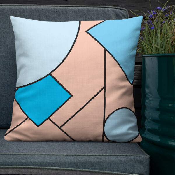 square pillow with an abstract design of blue and pink shapes sitting on a chair next to a plant