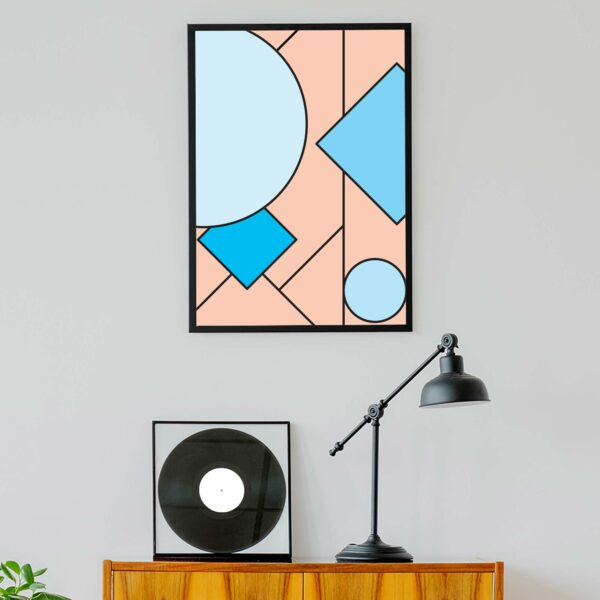 vertical fine art print with an abstract design of pink and blue shapes in a black frame hanging on a wall