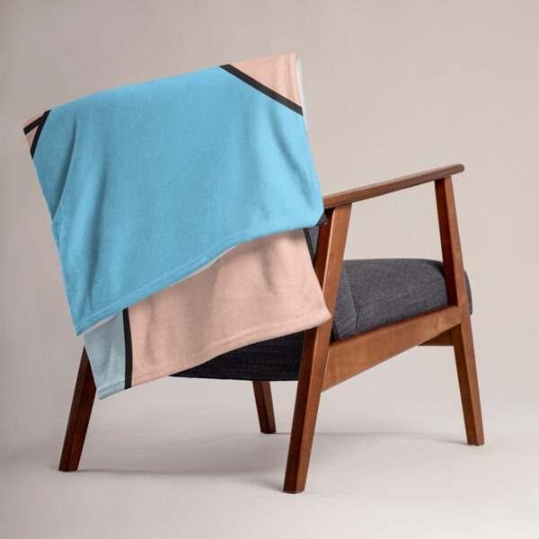 blanket with an abstract design of blue and pink shapes, draped over a chair