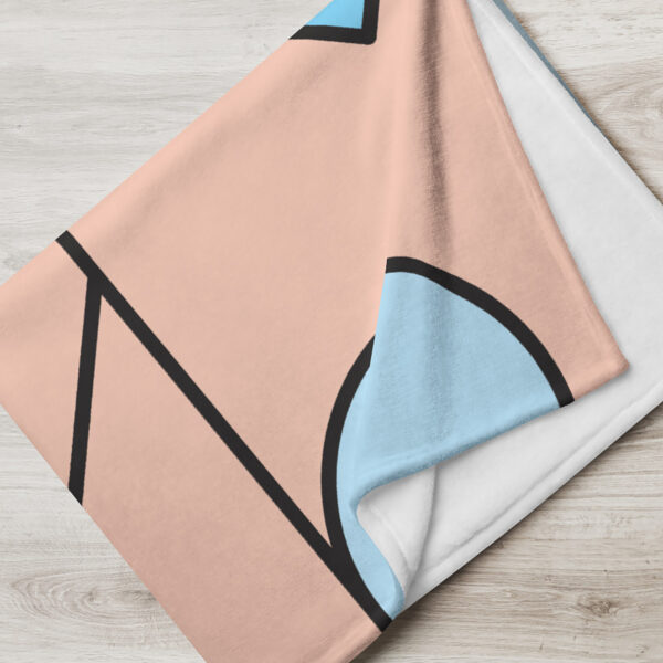folded blanket with an abstract design of blue and pink shapes