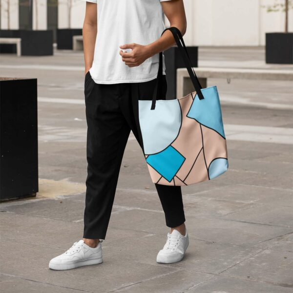 person holding a tote bag with an abstract design of pink and blue shapes and black handles