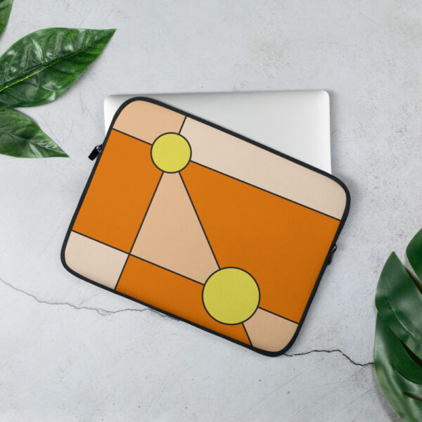 laptop sleeve with a minimalist design of two yellow circles on an orange background sitting on a table