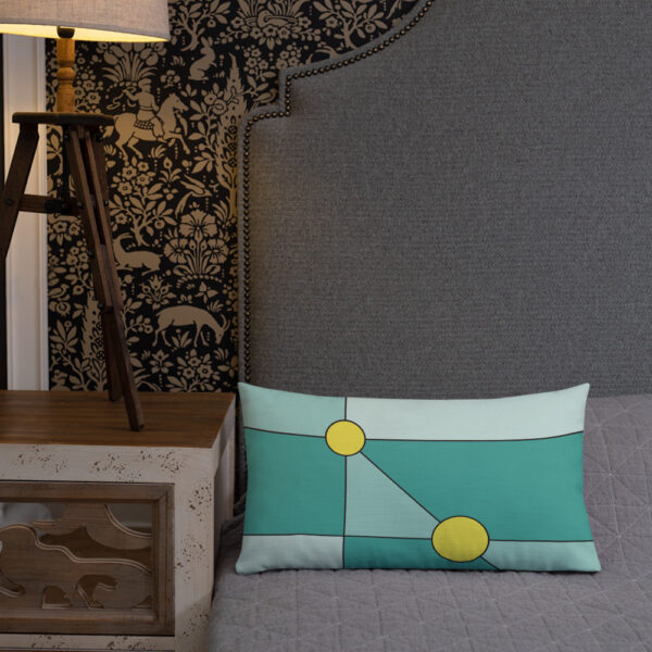 rectangle pillow with a minimalist design of two yellow circles on a teal blue background sitting on a bed