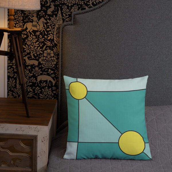 square pillow with a minimalist design of two yellow circles on a teal blue background sitting on a bed