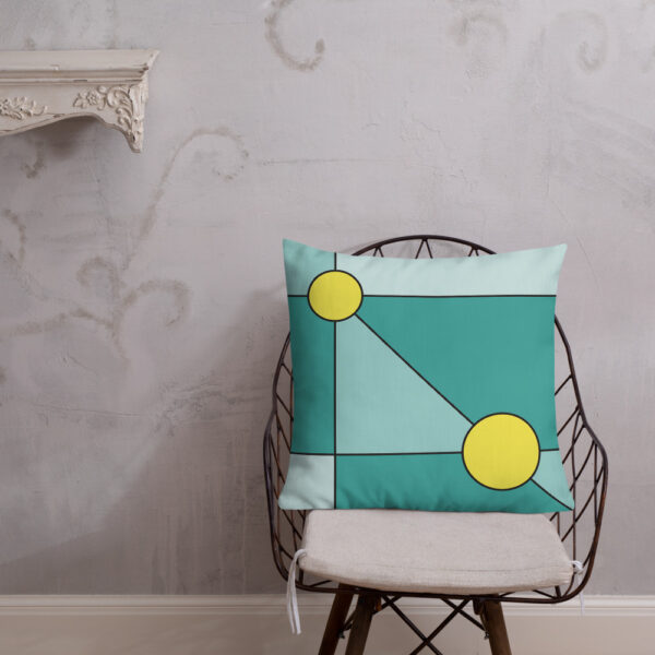 square pillow with a minimalist design of two yellow circles on a teal blue background sitting on a chair