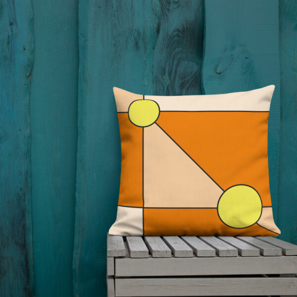 square pillow with a minimalist design of two yellow circles on an orange background sitting on a bench