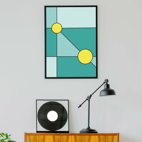 vertical fine art print with a minimalist design of two yellow circles on a teal blue background in a black frame hanging on a wall