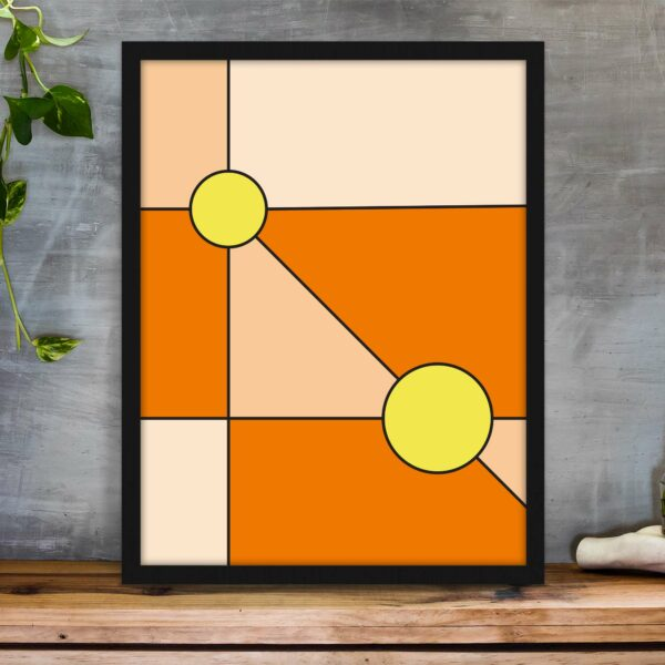 vertical fine art print with a minimalist design of two yellow circles on an orange background in a black frame sitting on a table