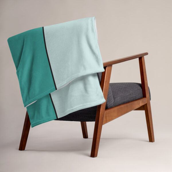 blanket with a minimalist design of two yellow circles on a teal blue background, draped over a chair