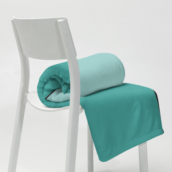 rolled up teal blue blanket sitting on a white chair