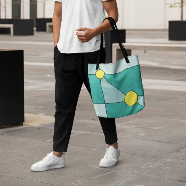 person holding a teal blue tote bag with two yellow circles in a minimalist design, with black handles
