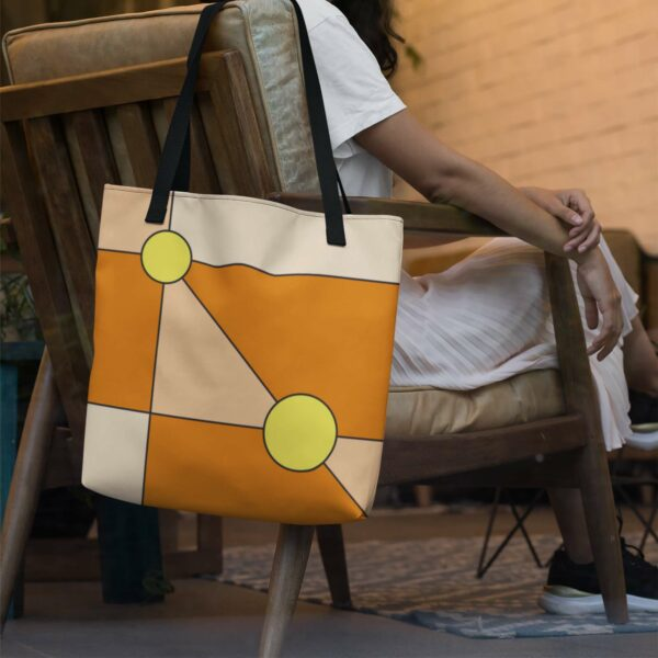 orange tote bag with two yellow circles in a minimalist design, with black handles, hanging on a chair