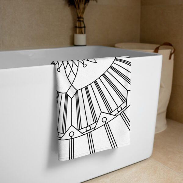 beach towel with a black and white geometric design draped over a bathtub