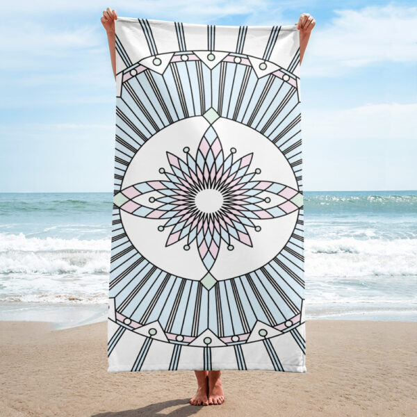person on a beach holding a beach towel with a pastel color geometric design