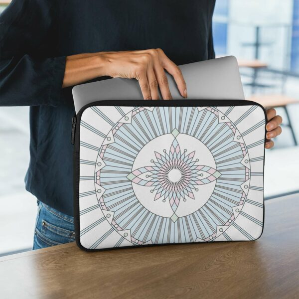 person holding a laptop sleeve with a geometric design of black lines and pastel colors on a white background