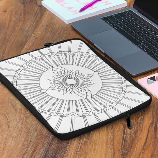 computer next to a laptop sleeve with a geometric design of black lines on a white background