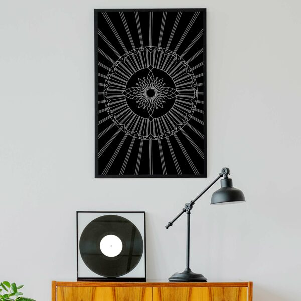 vertical fine art print with a black and white geometric design in a black frame hanging on a wall