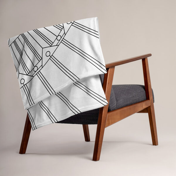 white blanket with a geometric design in black lines, draped over a chair