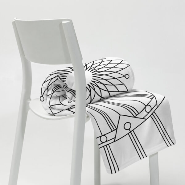 white blanket with a geometric design in black lines rolled up on a chair