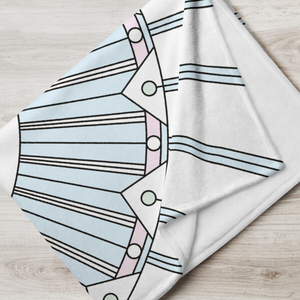 folded white blanket with a geometric design in black lines and pastel colors