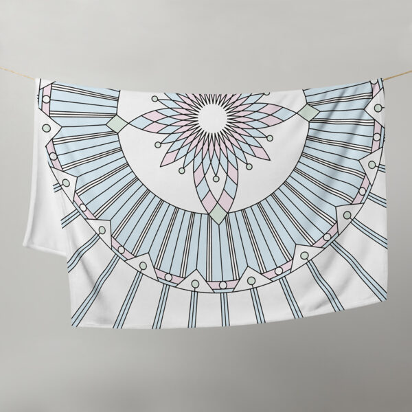 white blanket with a geometric design in black lines and pastel colors, hanging on a clothes line