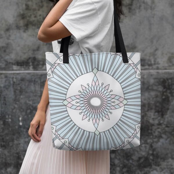 woman holding a white tote bag with a geometric black line design and pastel colors