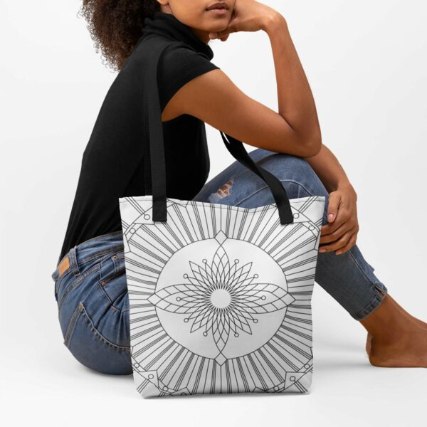 woman sitting with a white tote bag with a geometric black line design