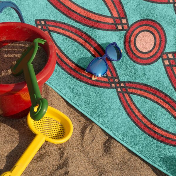 beach towel with a red geometric design on a blue background on sand with sunglasses