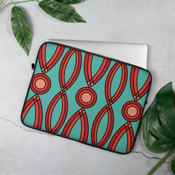 laptop sleeve with a geometric pattern of red shapes on a teal blue background sitting on a table