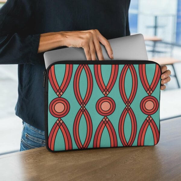 person holding a laptop sleeve with a geometric pattern of red shapes on a teal blue background